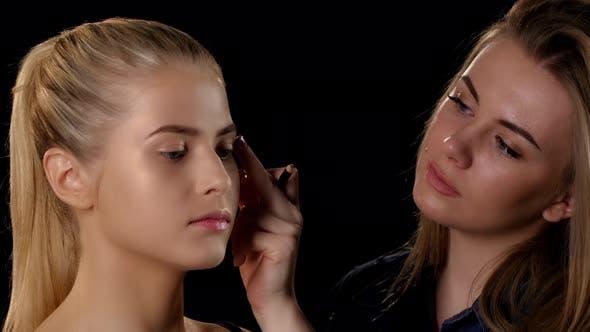 Thumbnail for Makeup Artist Applying Makeup To Young Blonde Girl. Black. Closeup