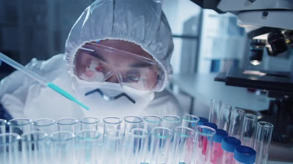 Thumbnail for Female Virologist Pouring Blue Liquid into Test Tube in Laboratory