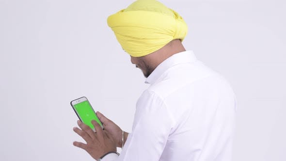 Cover Image for Rear View of Bearded Indian Sikh Businessman Using Phone