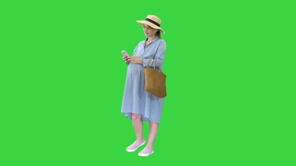 Pregnant Woman on the 9Th Month Using a Smartphone on a Green Screen, Chroma Key.