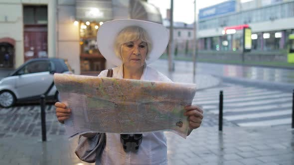Thumbnail for Senior Female Tourist Exploring Town with a Map in Hands. Looking for the Route
