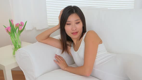 Thumbnail for Happy Chinese woman resting on couch
