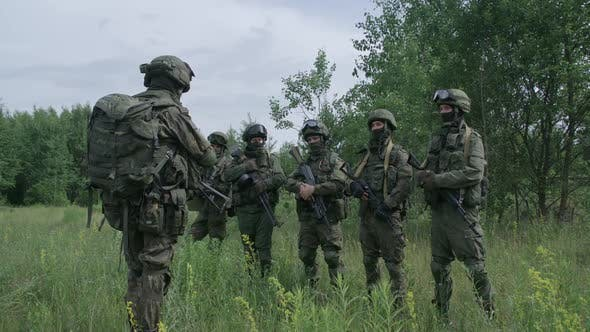Soldiers in Camouflage with Assault Rifles in Field Commander Instructs the Soldiers Military Action