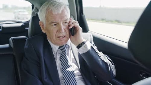 Senior Businessman with Mobile Phone in Car