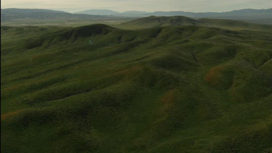 Thumbnail for Helicopter aerial shot tracking down green fields, overcast day