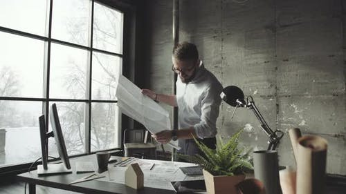 Young Architect in Stylish Loft Office Works with Documents