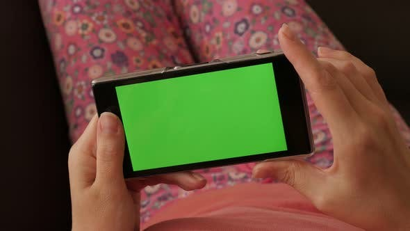Woman relaxing in home ambient while on green screen smartphone 4K 2160p 30fps UltraHD footage - fem