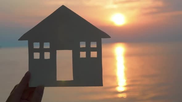 Cover Image for Hand Holding Cut Paper House Against of Sea at Sunset