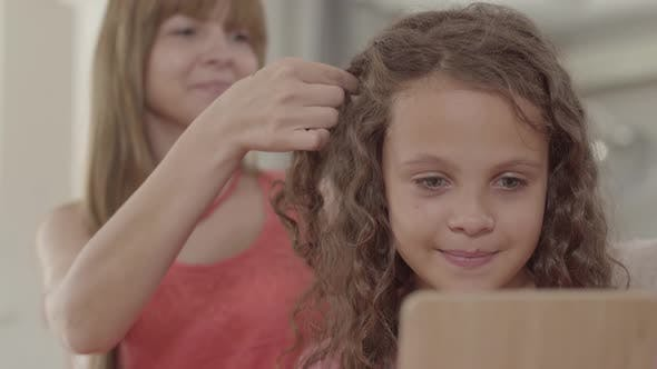 Thumbnail for Beautiful Young Mother Braids Her Cute Daughter Looking in the Mirror. Family Relationships