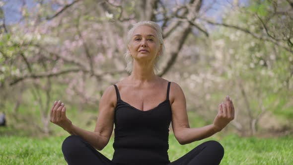 Front View of Confident Fit Senior Sportswoman Sitting in Lotus Pose Meditating in Spring Summer