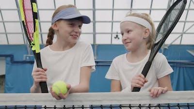 Portrait Of Little Girls On Tennis Court