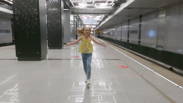 Cheerful Teenager Girl Dancing on Empty Platform Subway Station