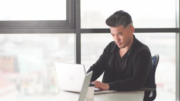 Thumbnail for Portrait of Asian Male Lawyer at His Desk in the Office Looking at His Personal Computer