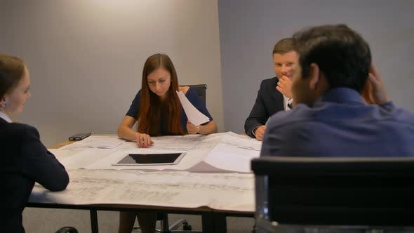 Group of Architects Working On a Project With Blueprints