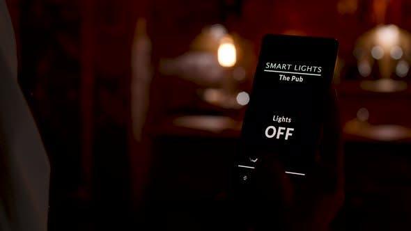 Barkeeper mit einer Smart Home-Anwendung, um das Licht einzuschalten