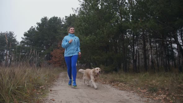Thumbnail for Sporty Fit Woman with Dog Jogging in Autumn Forest