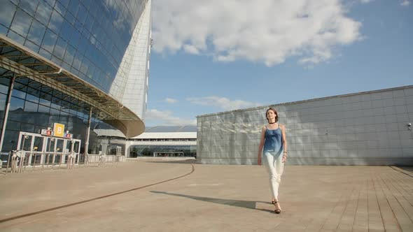 Thumbnail for Pretty Young Girl Walking In Highheels In A Long Light Dress Along The Huge Glass Building