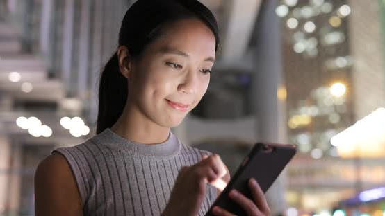 Cover Image for Woman using mobile phone in evening