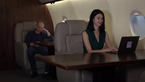 A Young Business Couple Flying In Their Private Jet Business Jet, A Girl Working At A Computer