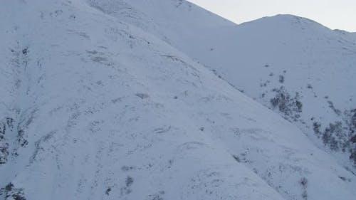 Nahaufnahme auf Alaska State Trooper Hubschrauber fliegen Hubschrauber vor den Bergen, Drohne Antenne foo