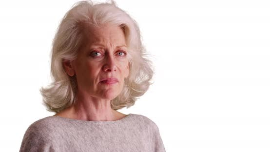 Close up of depressed older woman turning to frown at camera on white background