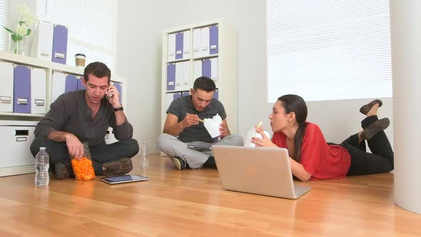 Thumbnail for Mexican and Caucasian employees eating food on floor of office