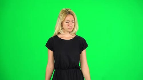 Pensive Woman Is Walking on a Green Screen at Studio. Slow Motion