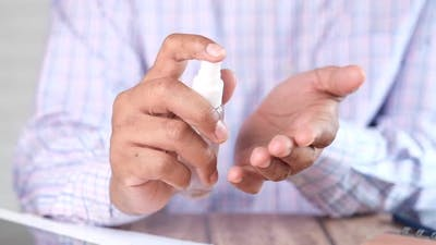 Close Up of Young Man Hand Using Hand Sanitizer Spray
