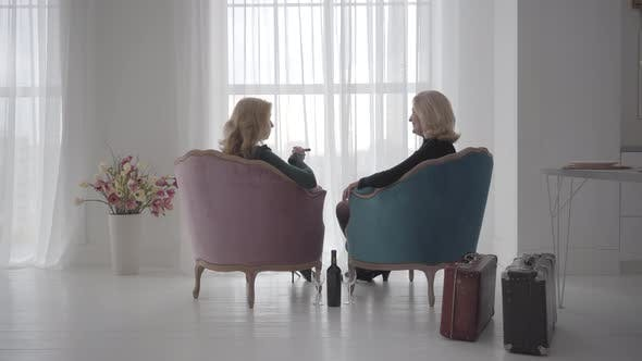 Thumbnail for Back View of Rich Mature Caucasian Women Sitting in Comfortable Armchairs and Talking