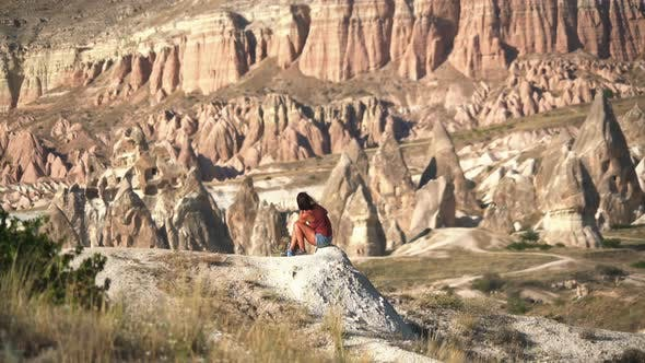 Woman Sitting by the Scenic View of Stunning Red Sandstone Hoodoos