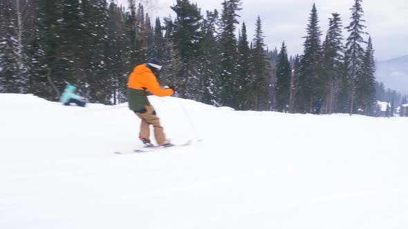 Thumbnail for Guy Skier Skies Down Snowy Mountain Slope Past Pine Trees