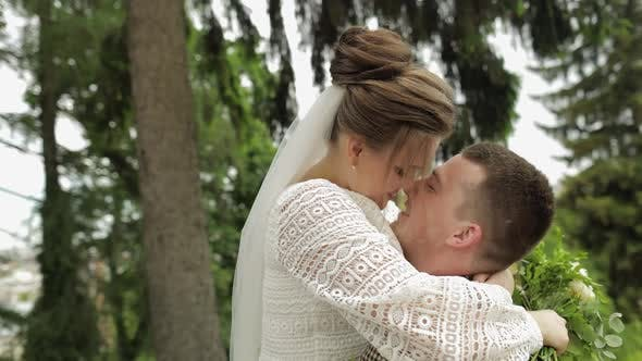 Thumbnail for Newlyweds. Caucasian Groom with Bride Kissing in Park. Wedding Couple. Man and Woman in Love