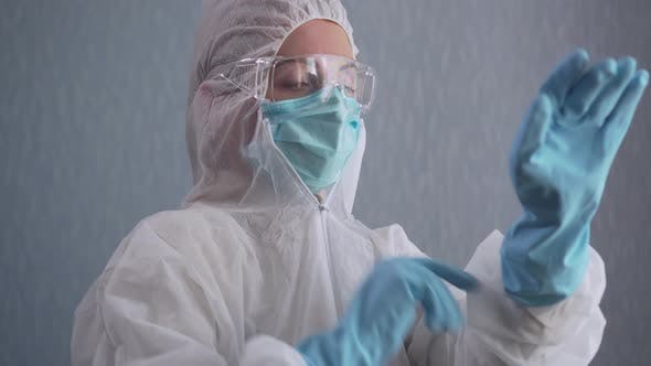 Medic in a Protective Suit Puts on Gloves.