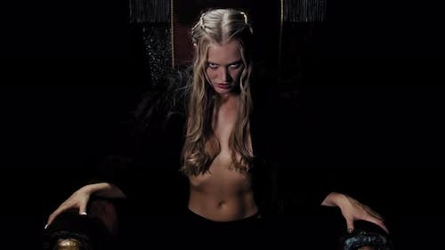 Blonde Medieval Princess Is Sitting on the Throne and Lifting Her Head