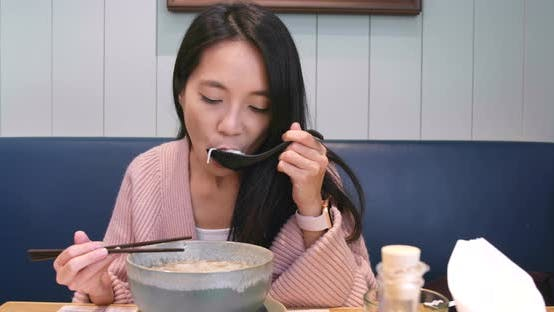 Thumbnail for Woman eating noodles in restaurant