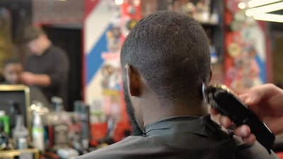 The Hairdresser Cuts the Client's Hair with a Hair Clipper
