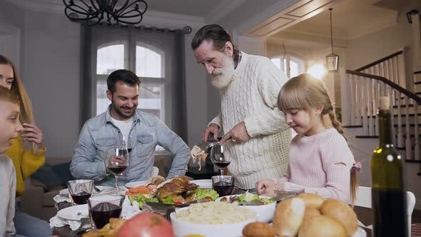 Thumbnail for Respected Senior Man Putting a Piece of Roast Turkey on Plate During Festive Family Dinner