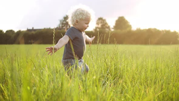 Thumbnail for Baby Boy Playing with the Grass Around Him with a Smile