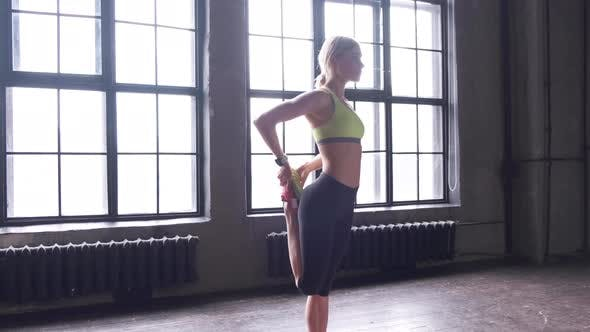 Side view a Young Athletic Blonde Woman doing a Warm up Stretching standing On a Mat