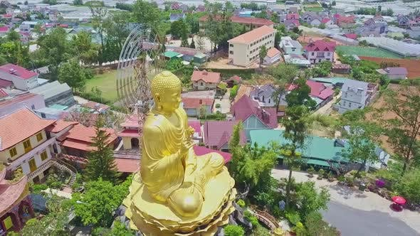 Thumbnail for Drone Rotates Above Large Buddha Monument Against Cityscape