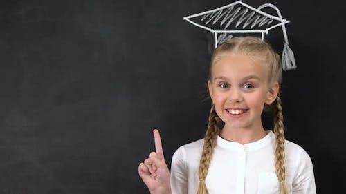Schoolgirl Pointing Finger at Blackboard, Academic Cap Painted Above Head