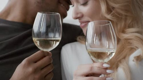 Loving Multicultural Couple Drinking Wine During Romantic Date Indoors Cropped