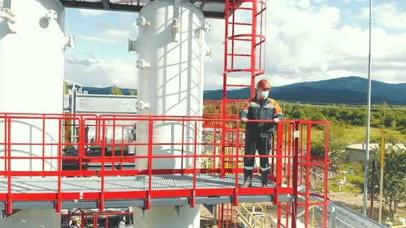 Aerial View Gas Station Operator Climbs To the Top of the Station. Modern Gas Complex in the