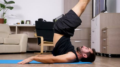 Fit Young Man Practicing Yoga Does Different Poses on the Floor