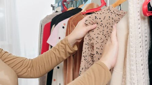 Closeup of Woman Moving Aside Clothes Hanging on Rack in Wardrobe and Choosing What To Wear