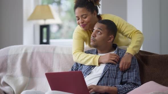 Beschäftigt Afroamerikaner Mann, der auf der Couch sitzt online als liebevolle Frau, die Ehemann umarmt