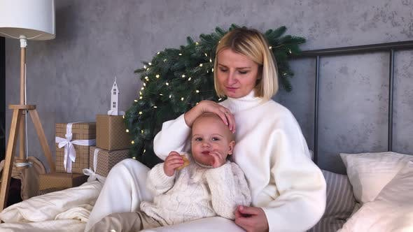 Mother's Christmas Mood with Her Child, Near the New Year Tree. Winter Holidays.