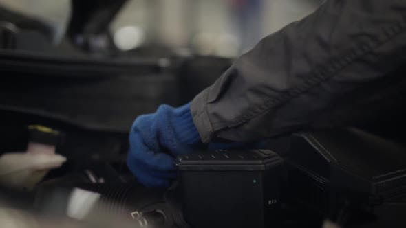 Thumbnail for Close-up of Male Hands in Protective Gloves Taking Off Engine Air Filter and Putting It Back Into