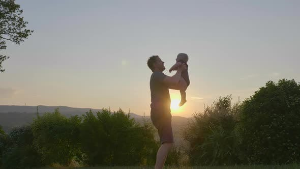 Thumbnail for Strong-willed Father Throwing and Catching His Jolly Baby Boy on a Sunset