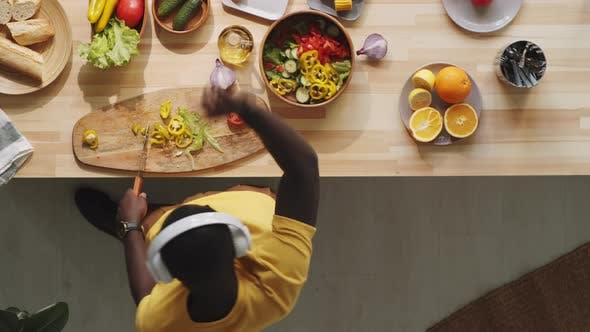 Afro-American Man Cooking Food and Dancing in Kitchen